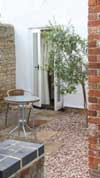 gravelled_sunken_courtyard_provides_suntrap_for_olive_tree