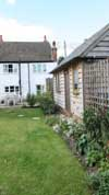 new_hand-built_oak_garage_contrasting_with_old_stone_cottage